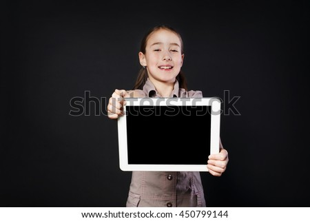 Little happy girl shows empty screen of white Digital Tablet, place for copy space. Female child studio portrait wih modern device at black background - stock photo