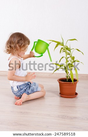 Little happy girl sits on the floor in a room and waters the plant . - stock photo