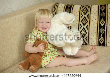 Little happy girl sitting at home on the couch and playing with teddy bears - stock photo