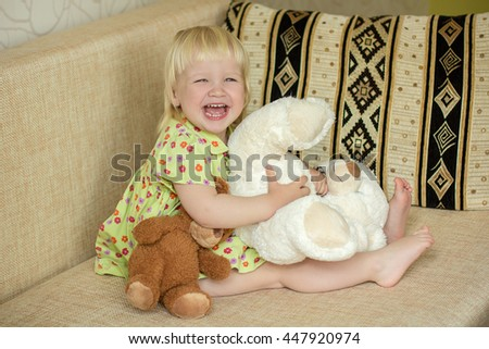 Little happy girl sitting at home on the couch and playing with teddy bears
