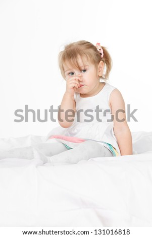Little happy girl sitting on the bed in white room