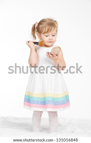 Little happy girl sitting on the bed in white room - stock photo