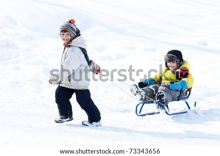 Little happy girl taking sled with little joyful boy, winter time - stock photo