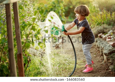 Little happy girl watering garden - stock photo