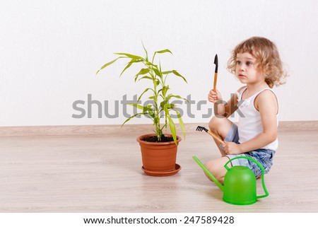 Little happy girl with a watering can, garden tools and a plant in flowerpot sits on the floor in a room. - stock photo