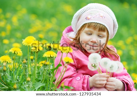little happy girl with dandelion on spring summer field - stock photo