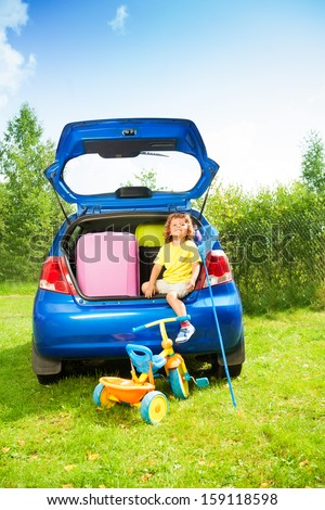 Little happy laughing 3 years old boy sitting in the car trunk with bags, net-scoop, tricycle and mate for the trip in the car waiting for the parents to drive - stock photo