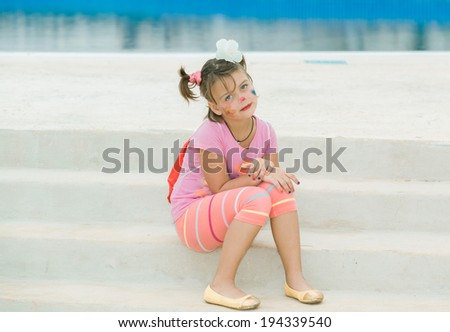 little happy peaceful girl with funny face make-up,  sitting on white concrete steps and looking at camera near the swimming pool edge - stock photo