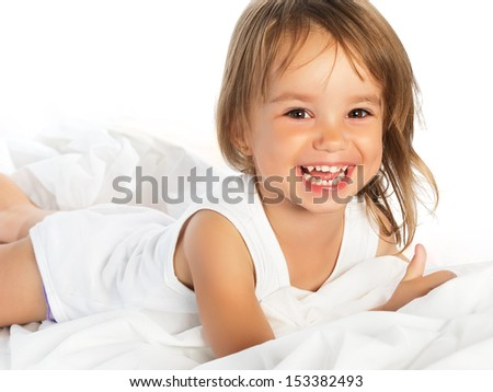 little happy smiling cheerful girl in a white bed isolated
