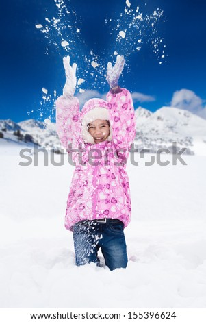 Little happy smiling girl in pink throws snowin the air with snawflakes flying in all directions - stock photo