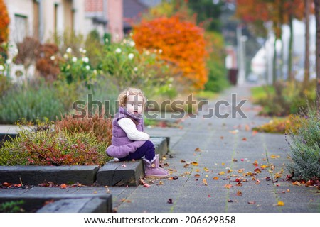 Little happy toddler girl in a warm purple jacket and boots playing in a beautiful city street with golden fall garden trees on a warm nice autumn day - stock photo