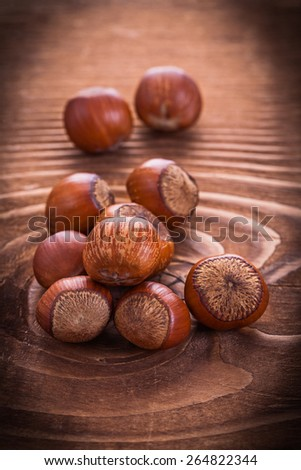 little heap of hazelnuts on vintage wooden board food and drink still life  - stock photo