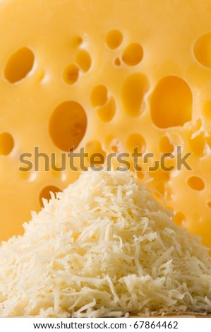 Little hill of cheese shredded shavings with big porous chunk on background - stock photo
