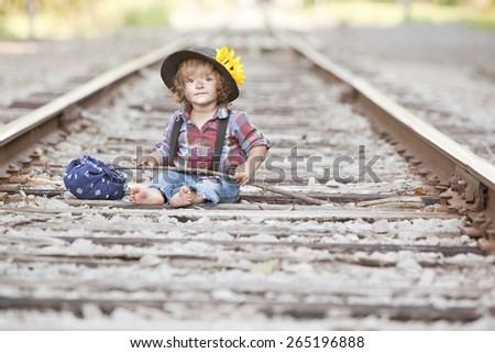 Little Hobo.  Adorable toddler dressed as a hobo and sitting on the railroad tracks. - stock photo