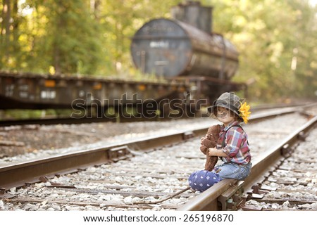 Little Hobo.  Adorable toddler dressed as a hobo and sitting on the railroad tracks.  Room for your text. - stock photo