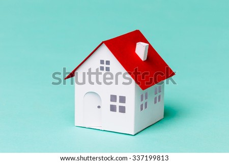 Little house made of paper on a blue background.