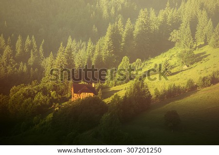Little house on a green mountain slope, natural landscape vintage background - stock photo