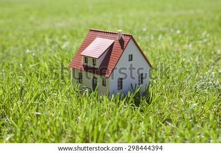Little house on green grass  - stock photo
