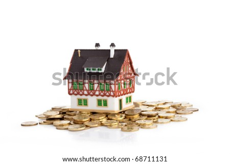Little house on pile of coins - stock photo