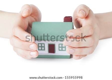 Little house toy covered by hands over white background - stock photo