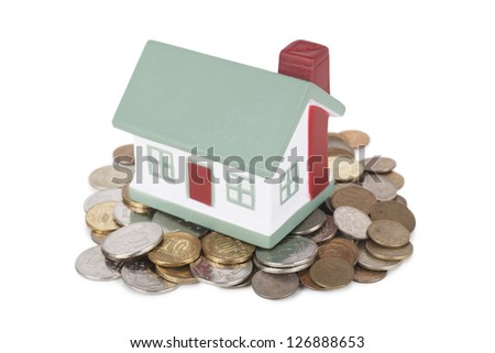Little house toy on a heap of coins isolated over white background