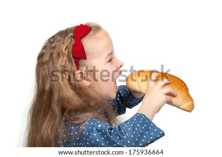 Little hungry girl biting a bun isolated on white background - stock photo