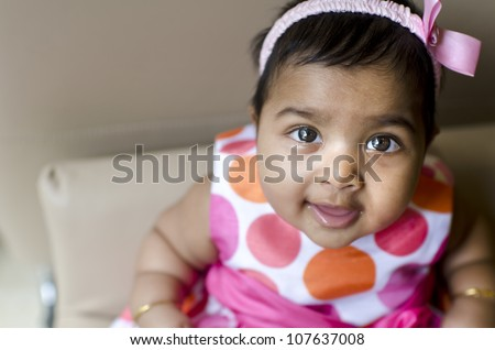 little indian baby girl resting on the arm of sofa seat, shallow dof, focus on eyes - stock photo