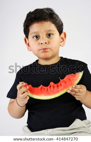 Little Indian boy eating watermelon on white background - stock photo