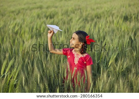 Little Indian girl holding a paper aero plane standing in wheat field - stock photo