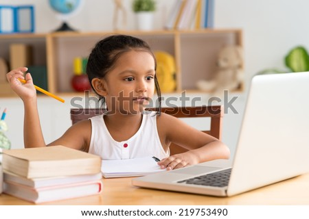 Little Indian girl looking at the laptop while doing homework - stock photo