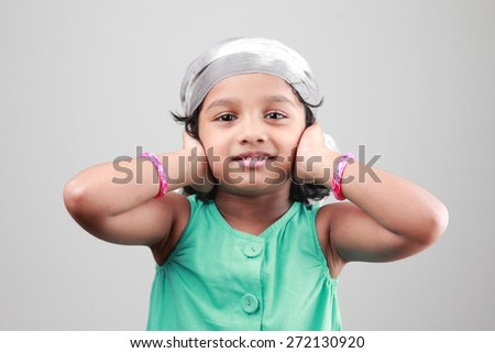Little Indian girl poses with hands on her ears - stock photo