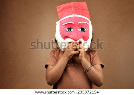 Little Indian girl wears a mask of Santa - stock photo