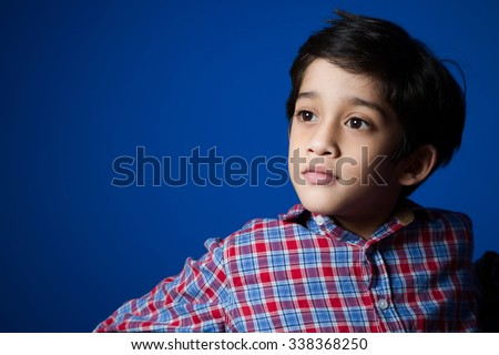 Little Indian kid posing in-front of a blue wall.  - stock photo