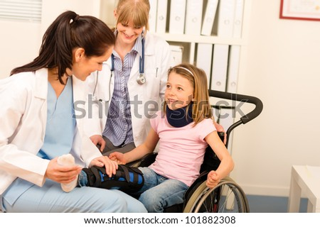 Little injured girl on wheelchair with doctors at medical office - stock photo