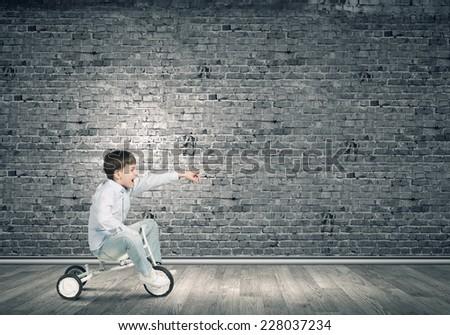 Little joyful cute boy riding tricycle in empty room - stock photo
