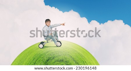 Little joyful cute boy riding tricycle on green grass - stock photo