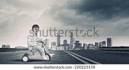 Little joyful cute boy riding tricycle on road - stock photo