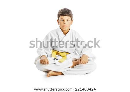 Little karate kid sitting legs crossed on white background - stock photo