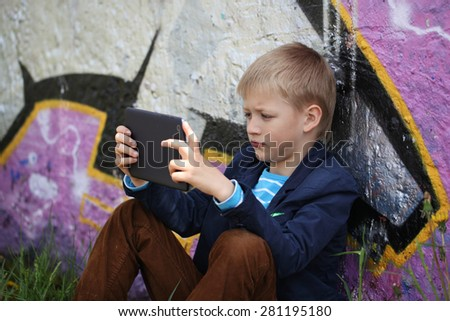Little kid  absorbed into his tablet for educating and playing.Boy sitting near a wall  graffiti. - stock photo