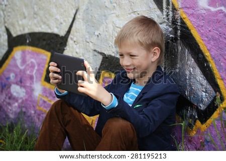 Little kid  absorbed into his tablet for educating and playing.Boy sitting near a wall  graffiti.