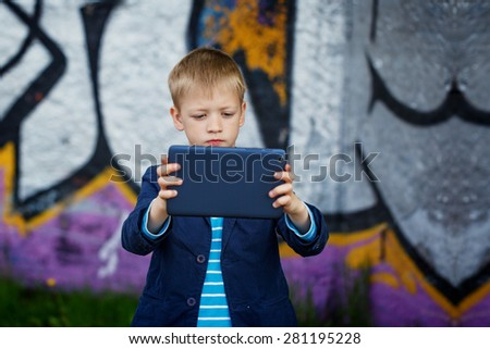 Little kid  absorbed into his tablet for educating and playing.Boy standing near a wall  graffiti. - stock photo