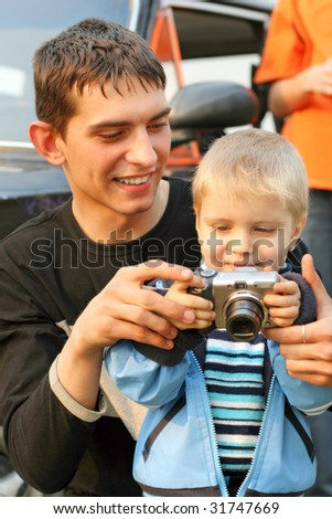 little kid and teenager with a camera - stock photo