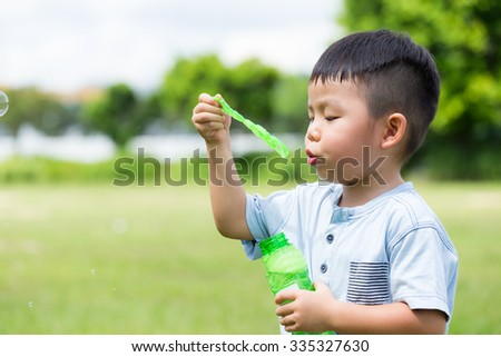 Little kid blowing soap bubbles