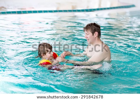 Little kid boy and his father swimming in an indoor swimming pool. Active happy kid boy wearing safe swimmies. Family time.
