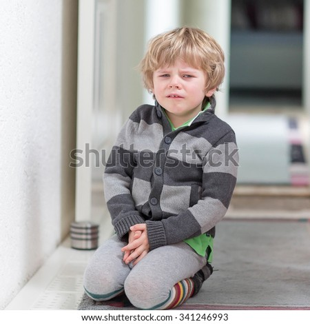 Little kid boy crying at home and showing sad mood, indoors.