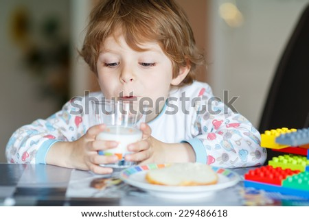 Little kid boy drinking milk, eating breakfast and playing with colorful construction blocks, at home indoors. - stock photo
