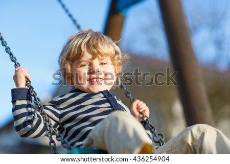 Little kid boy having fun and swinging on outdoor playground. Happy smiling child enjoying summer time. Carefree childhood concept. - stock photo
