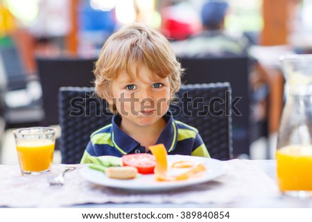 Little kid boy having healthy breakfast in hotel restaurant or city cafe. Cute child drinking juice and eating fresh vegetables - stock photo
