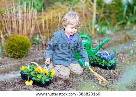 little kid boy helping with gardening in spring garden funny child planting flowers family