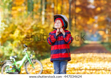 Little kid boy in colorful clothes in autumn park with a bicycle. Active child putting his bike helmet. Safety, sports, leisure with kids concept. - stock photo